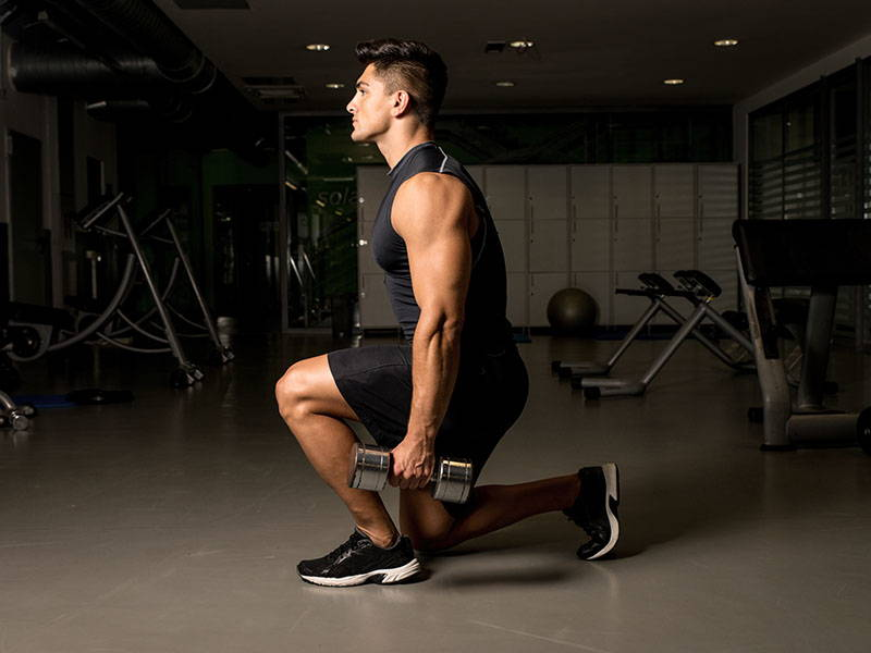 Man lunging with dumbbells