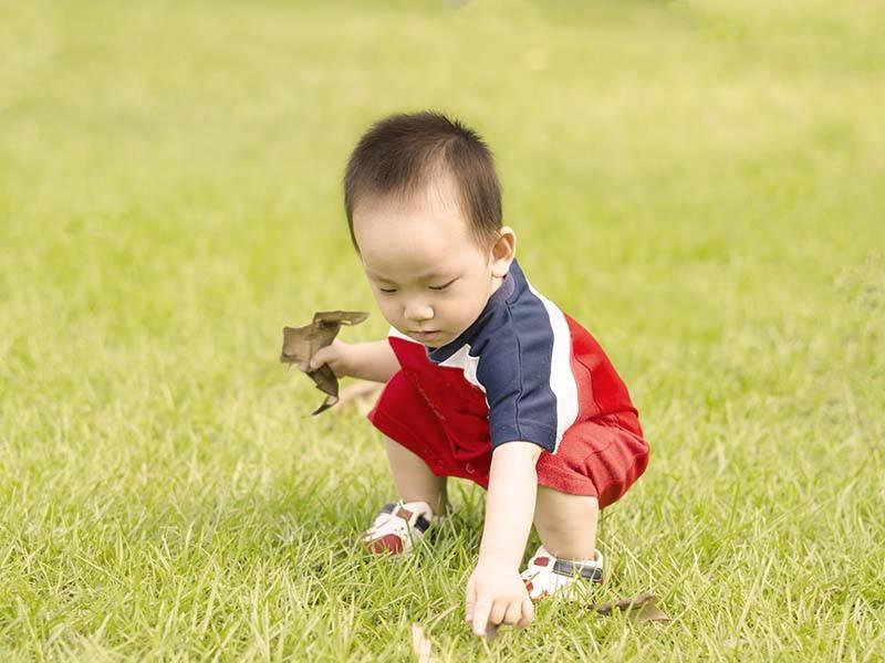 Kid Squatting In Grass